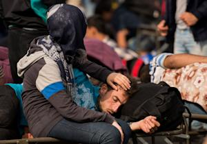 Migrants rest after they arrived at the border between…
