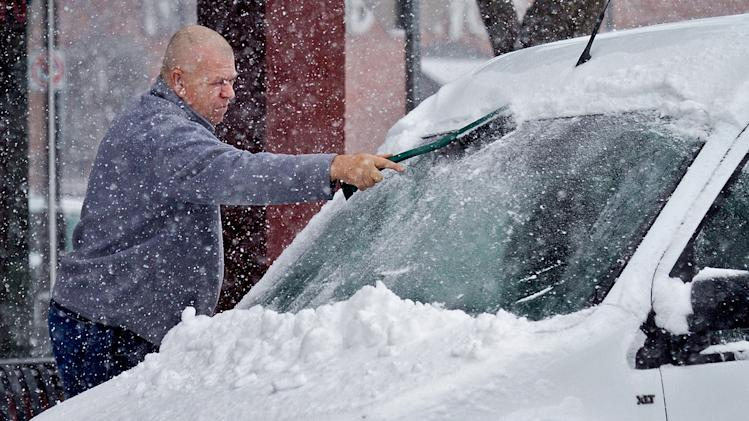 A wichita driver clears snow from his windshield in Wichita, Kan. Wednesday, Feb. 20, 2013. (AP Photo/The Wichita Eagle, Mike Hutmacher)