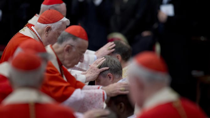 Pope Benedict XVI personal secretary Georg Ganswein, center, is blessed by cardinals and bishops after he was named bishop during an Epiphany mass in St.Peter's Basilica at the Vatican, Sunday, Jan. 6, 2013. The Epiphany day, is a joyous day for Catholics in which they recall the journey of the Three Kings or Magi to pay homage to Baby Jesus. (AP Photo/Andrew Medichini)