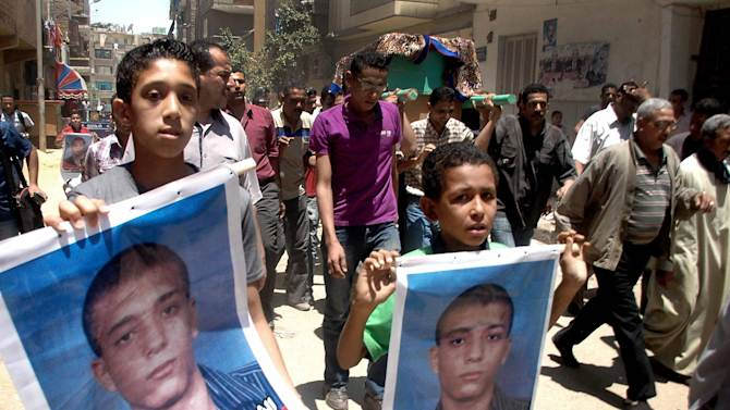 Egyptian boys hold posters of Ahmed Hussein Eid who was fatally stabbed by three bearded men during his funeral procession in the city of Suez, Egypt, Wednesday, July 4, 2012. The murder of a university student by suspected militants as his girlfriend looked on is fueling fears in Egypt that vigilante groups seeking to enforce a strict interpretation of Islam's teachings may be feeling confident with an Islamist president in office to take over the streets. (AP Photo)