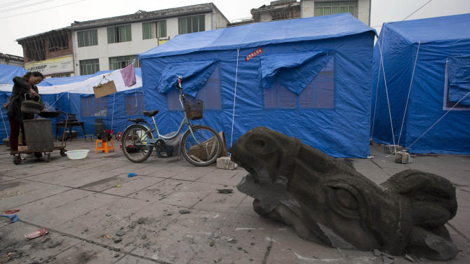 The head of a horse statue decapitated by Saturday's earthquake sits near tents set up for residents displaced by the quake in Lushan county  in southwestern China's Sichuan province, Monday, April 22, 2013. Saturday's earthquake in Sichuan province killed at least 186 people, injured more than 11,000 and left nearly two dozen missing, mostly in the rural communities around Ya'an city, along the same seismic fault where a devastating quake to the north killed more than 90,000 people in Sichuan and neighboring areas five years ago in one of China's worst natural disasters.  (AP Photo/Ng Han Guan)