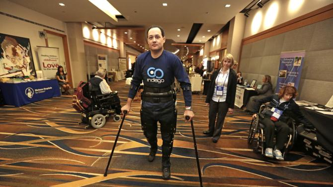In this May 6, 2013 photo, Michael Gore, center, who is paralyzed from a spinal injury, walks with the use of the Indego wearable robot under the supervision of physical therapist Clare Hartigan during a meeting of the American Spinal Injury Association at a downtown hotel in Chicago. Eleven years ago, Gore was paralyzed from the waist down in a workplace accident, but with the aid of the 27-pound gadget that snaps together from pieces that fit into a backpack he stands and walks with the assistance of science and engineering. The device is among several competing products that hold promise for people with spinal injuries, like Gore, and for people with multiple sclerosis and cerebral palsy or for those recovering from strokes. (AP Photo/M. Spencer Green)