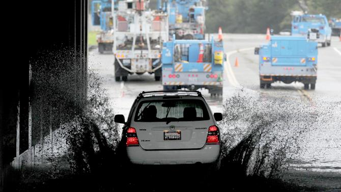 A vehicle transits a flooded underpass in San Rafael, Calif., on Sunday, Dec. 2, 2012, as utility workers work to repair a downed power line. Although sunny skies reappeared throughout the region Sunday afternoon, flood warnings remain for several rivers. (AP Photo/Noah Berger)