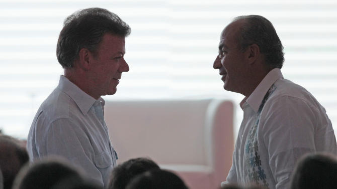 Colombia's President Juan Manuel Santos, left, greets Mexico's President Felipe Calderon at the inauguration of the 2012 CEO Summit of the Americas in Cartagena, Colombia, Friday April 13, 2012. Regional business leaders are meeting to discuss trade and investment opportunities in Latin America. The summit is being held parallel to the sixth Summit of the Americas' meeting for leaders of the Western Hemisphere. (AP Photo/Fernando Llano)