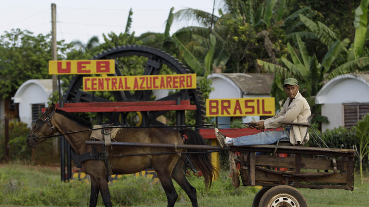 "In this Sept. 8, 2012 photo, a man rides in a horse-drawn carriage outside the sugar processing plant ""Brasil"" in Jaronu, Cuba.  Just two years ago, Cuba's sugar industry was on its knees after the worst harvest in more than a century. Now Cuba's signature industry is showing signs of life. Hulking processing plants are coming back online, and the harvest is growing by double digits each year, a boon to rural towns like Jaronu. (AP Photo/Franklin Reyes)"