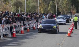 Fans crowd the scene of a memorial rally and car cruise…