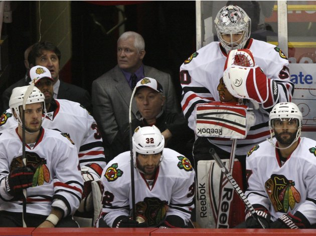 Blackhawks goalie Corey Crawford stands on the bench behind teammates during the final seconds of Game 4