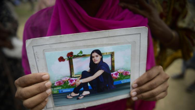 A Bangladeshi woman holds a photograph of her missing sister at a makeshift morgue near the site of a garment factory building that collapsed in Savar near Dhaka, Bangladesh, Wednesday May 8, 2013. Dozens of bodies recovered Wednesday from the building were so decomposed they were being sent to a lab for DNA identification, police said, as the death toll from Bangladesh's worst industrial disaster topped 800. (AP Photo/Ismail Ferdous)