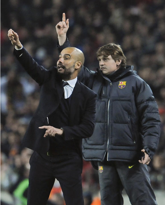 In this Tuesday April 3, 2012 photo FC Barcelona's coach Pep Guardiola, left, gives instruction to his team as FC Barcelona's assistant coach Tito Vilanova, right behind, gestures, during their Europa