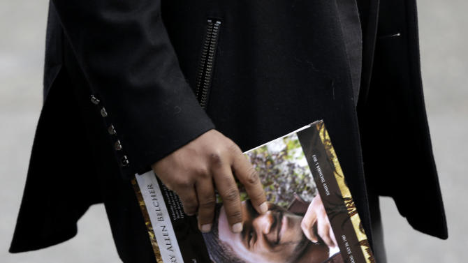 A man carries a program with a photo of Jovan Belcher that was given out at Belcher's funeral in Dix Hills, N.Y., Wednesday, Dec. 12, 2012. Several hundred mourners have gathered for the funeral of Kansas City Chiefs linebacker Jovan Belcher near his hometown on Long Island. The 25-year-old Belcher shot and killed his girlfriend and then himself Dec. 1. (AP Photo/Seth Wenig)
