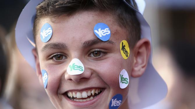 "A young ""Yes"" supporter smiles as he supports Scotland's First Minister Alex Salmond as he campaigns through Largs, Ayrshire"
