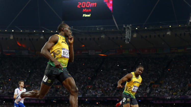 Jamaica's Usain Bolt, center, crosses the finish line to win gold ahead of Jamaica's Yohan Blake, right, and France's Christophe Lemaitre, left, in the men's 200-meter final during the athletics in the Olympic Stadium at the 2012 Summer Olympics, London, Thursday, Aug. 9, 2012. (AP Photo/Matt Dunham)