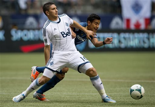 Vancouver Whitecaps' Johnny Leveron, left, of Honduras, prevents Los Angeles Galaxy's Jose Villarreal from getting to the ball during the first half of an MLS soccer game in Vancouver, British Columbi
