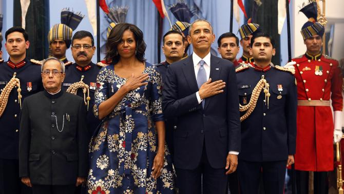 U.S. President Obama and first lady Michelle place their hands over their hearts during the U.S. National Anthem with India's President Mukherjee at the Rashtrapati Bhavan presidential palace in New Delhi