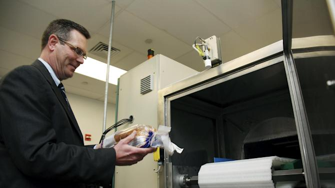 In this Dec. 6, 2012, photo, Don Stull, chief executive officer of Microzap, Inc., places a loaf of bread inside a patented microwave that kills mold spores in Lubbock, Texas. The company claims the technology allows bread to stay mold-free for 60 days. (AP Photo/John Mone)