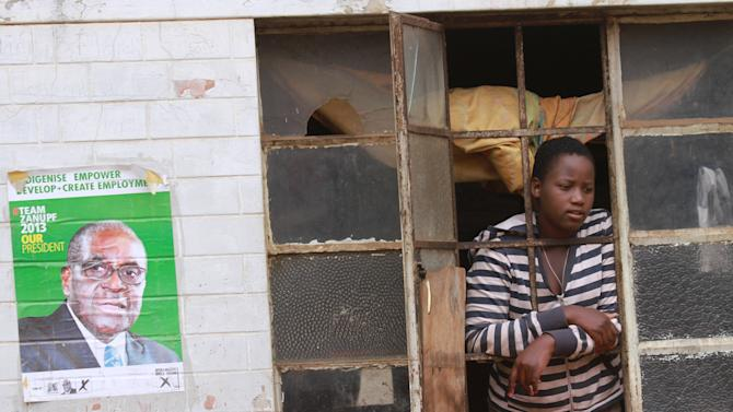 A woman looks through her window in Mbare, Harare, Monday, August, 5, 2013. Zimbabwean President Robert Mugabe, 89, won another mandate to rule the country for the next five years after receiving more than 60 percent of the vote beating his main challenger Morgan Tsvangirai who has declared the election null and void and vowed to fight the outcome in courts.(AP Photo/Tsvangirayi Mukwazhi)