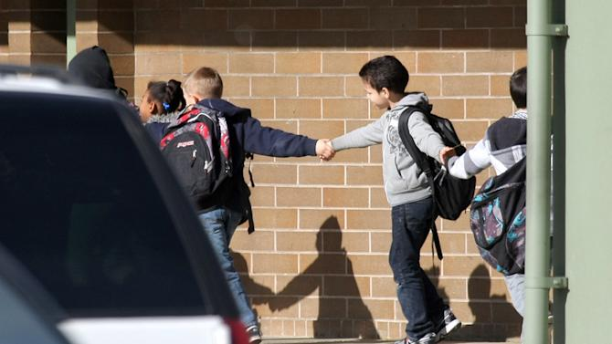 Students hold hands as they are led along a walkway at Armin Jahr Elementary School following a shooting there Wednesday, Feb. 22, 2012, in Bremerton, Wash. An 8-year-old girl was shot in the abdomen at the school and one of her classmates was detained, authorities said. The injured third-grader was airlifted to Seattle's Harborview Medical Center. Authorities said a third-grade boy was being questioned and a firearm was found in a classroom. (AP Photo/Kitsap Sun, Larry Steagall)