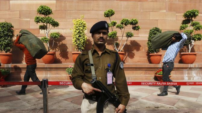 Men carry sacks containing the 2015/16 federal budget papers as an Indian security personnel stands guard at the parliament in New Delhi