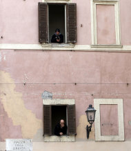 "People peer out of windows of a building facing the papal summer residence in Castelgandolfo, in the outskirts of Rome, Saturday, March 23, 2013. Pope Francis has traveled to Castel Gandolfo to have lunch with his predecessor Benedict XVI in a historic and potentially problematic melding of the papacies that has never before confronted the Catholic Church. The Vatican said the two popes embraced on the helipad. In the chapel where they prayed together, Benedict offered Francis the traditional kneeler used by the pope. Francis refused to take it alone, saying  ""We're brothers,"" and the two prayed together on the same one. (AP Photo/Gregorio Borgia)"
