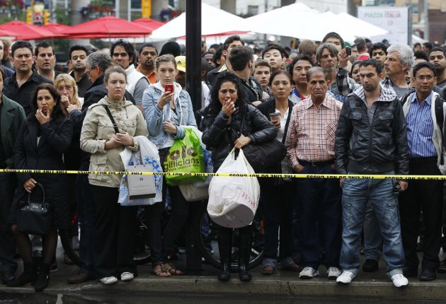 People stand outside the Toronto Eaton Centre shopping mall in Toronto, June 2, 2012. Three people were said to be wounded, at least one seriously, in a shooting at Toronto's Eaton Centre, one of the city's top tourist destinations and its main downtown mall, local media reported on Saturday. Shots were heard in the mall's food court and the entire mall was being evacuated, reports said.