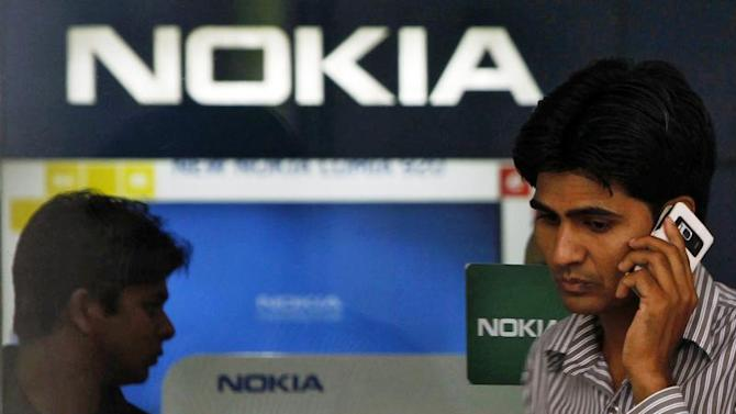 A customer speaks on his mobile phone as he comes out of a Nokia showroom in New Delhi