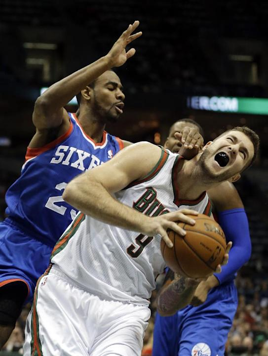 Milwaukee Bucks' Miroslav Raduljica (9) is fouled as he goes up for a shot against Philadelphia 76ers' Elliot Williams during the second half of an NBA basketball game Saturday, Dec. 21, 2013,