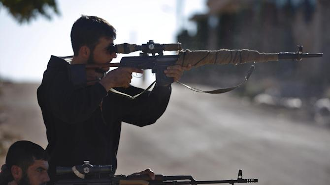 Syrian rebel snipers aim at Syrian army positions on the outskirts of Aleppo, Syria Wednesday, Nov. 14, 2012. (AP Photo/Khalil Hamra)