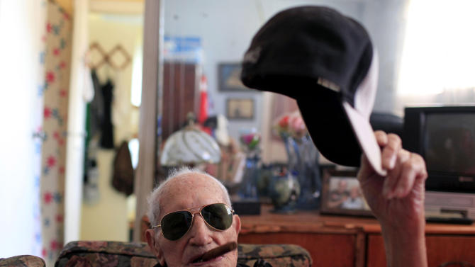 In this April 23, 2013 photo, Conrado Marrero, the world's oldest living former major league baseball player, poses for a photo as he holds his baseball cap and an unlit cigar in his mouth two days before is 102nd birthday at his home in Havana, Cuba. In addition to his longevity, the former Washington Senator has much to celebrate this year. After a long wait, he finally received a $20,000 payout from Major League baseball granted to old-timers who played between 1947 and 1979. The money had been held up since 2011 due to issues surrounding the 51-year-old U.S. embargo on Cuba, which prohibits most bank transfers to the Communist-run island. But the payout finally arrived in two parts, one at the end of last year, and the second a few months ago, according to Marrero's family. (AP Photo/Franklin Reyes)