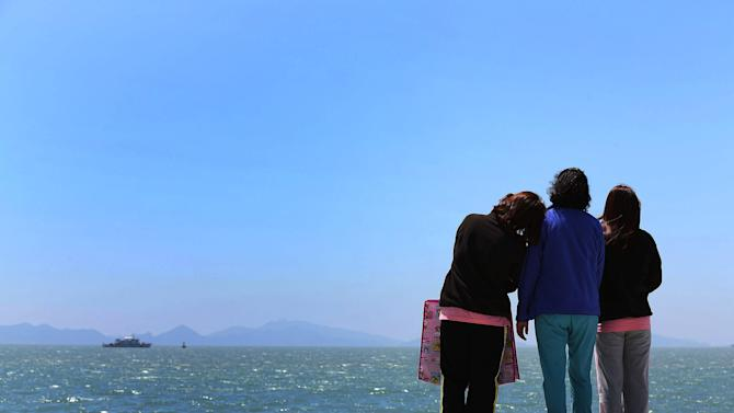 Relatives of a passenger aboard the sunken Sewol ferry look toward the sea at a port in Jindo, South Korea, Wednesday, April 30, 2014. South Korea's president apologized Tuesday for the government's inept initial response to a deadly ferry sinking as divers fought strong currents in their search for nearly 100 passengers still missing nearly two weeks after the accident.(AP Photo/Yonhap) KOREA OUT