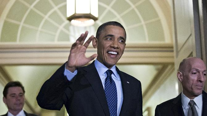 President Barack Obama, escorted by House Sergeant at Arms Paul Irving, right, waves as he arrives on Capitol Hill in Washington, Wednesday, March 13, 2013, for closed-door talks with House Speaker John Boehner and the House Republican Conference to discuss the budget. (AP Photo/J. Scott Applewhite)