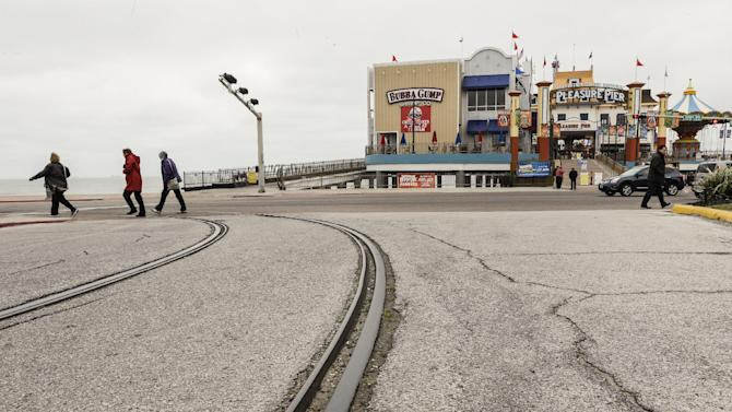 Tourists walk over some tracks along Seawall Boulevard near Pleasure Pier on Tuesday, Feb. 24, 2015, in Galveston, Texas. The island city's Trolley cars were destroyed during Hurricane Ike. On Thursday, Feb. 26, 2015,  the City Council is taking a vote to use the old track cars or use gas powered wheeled trolley cars. (AP Photo/Houston Chronicle,  Brett Coomer) MANDATORY CREDIT
