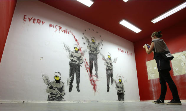 A women takes a picture of an artwork of British street artist Banksy in Berlin, Germany, Tuesday, Sept. 13, 2011. The graffiti showing five soldiers with angel's wings and yellow smiley faces beneath