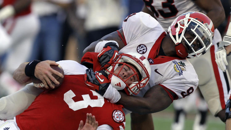 Georgia linebacker Alec Ogletree (9) sacks Nebraska quarterback Taylor Martinez (3) on a fourth and nine play late in the fourth quarter of the Capital One Bowl NCAA college football game, Tuesday, Jan. 1, 2013, in Orlando, Fla. Georgia won 45-31. (AP Photo/John Raoux)