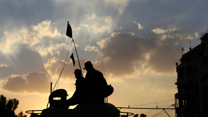 Egyptian army soldiers sit on top of their tank as the sun sets outside the presidential palace, background, in Cairo, Egypt, Saturday, Dec. 8, 2012. Egypt's military warned Saturday of 'disastrous consequences' if the crisis that sent tens of thousands of protesters back into the streets is not resolved, signaling the army's return to an increasingly polarized and violent political scene.(AP Photo/Hassan Ammar)