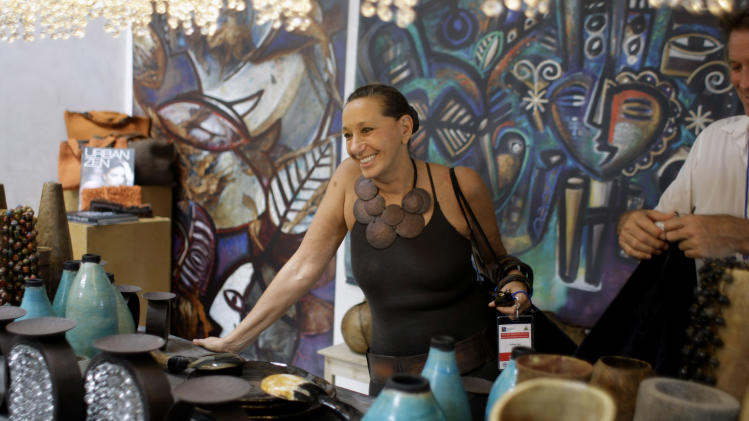 ** ADDS DAY AND DATE ** American fashion designer Donna Karan smiles as she stands before a display of Haitian pottery at the Caracol Industrial Park, in Caracol, Haiti, Monday, Oct. 22, 2012. The Haitian government will host Hillary and Bill Clinton, a delegation of foreign investors and a crowd of celebrities including Karan, Sean Penn and Ben Stiller, Monday, to showcase the marquee project of the U.S. aid effort since the 2010 earthquake. The Clintons and their allies hope the $300 million facility will transform the northern part of this impoverished country by providing thousands of desperately needed jobs. (AP Photo/Dieu Nalio Chery)