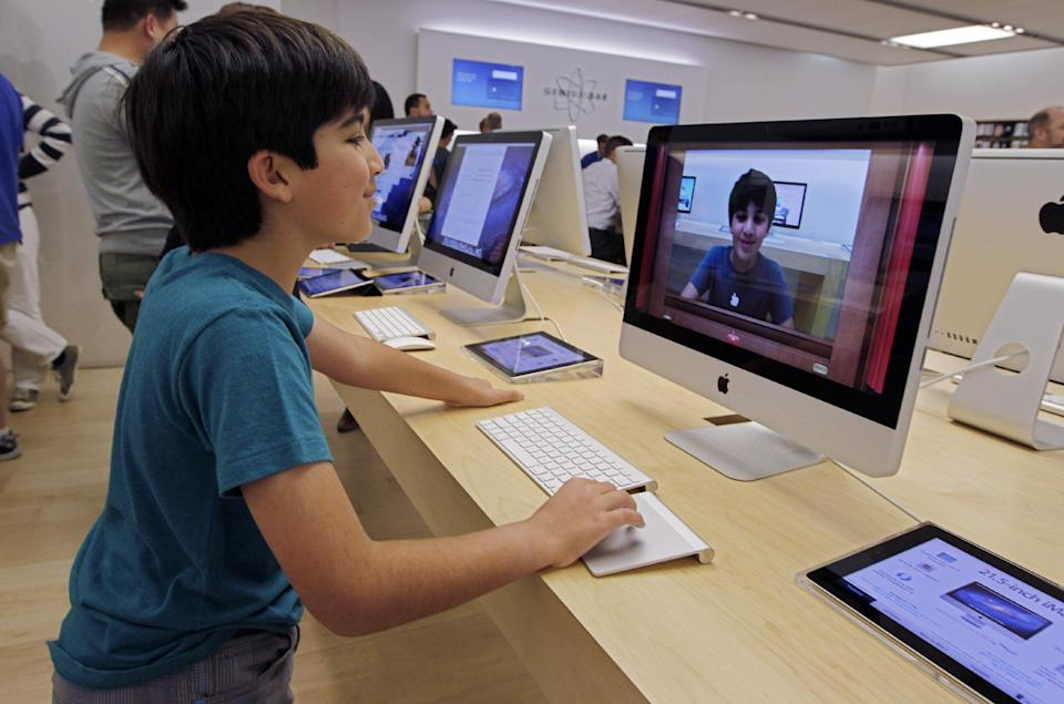 In this  Thursday, July 19, 2012, photo an Apple customer Shayan Hooshmand, 11, uses PhotoBooth on a 21.5-inch iMac at an Apple store in Palo Alto, Calif. Apple Inc. reports quarterly financial results after the market closes on Tuesday, July 24. (AP Photo/Paul Sakuma)