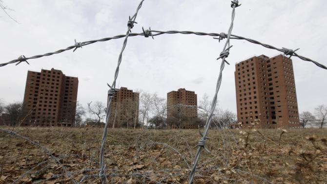 """Part of the Brewster-Douglass housing project site is shown in Detroit, Friday, March 18, 2011.  If Detroit Housing Commission director Eugene Jones  had his way the """"for sale"""" sign he'd post off Interstates 75 and 375 would read: """"14 acres of prime real estate between the city's resurgent downtown and promising Midtown. A steal at $9 million. Will accept reasonable offer."""" Real offers have been few. One arts group proposal to hang junked cars from windows in one the Brewster-Douglass housing project's empty 14-story towers was declined. Unlike cities like Chicago, where the last building in notorious Cabrini-Green public housing complex was razed within months of the final family moving out, Brewster-Douglass has been empty for two years and none of the 20 brick buildings has been torn down. Neither the city nor Jones' commission has the money to demolish the complex which is beginning to rival the long-empty, 17-story Michigan Central Depot as another symbol of Detroit's decay. (AP Photo/Paul Sancya)"""