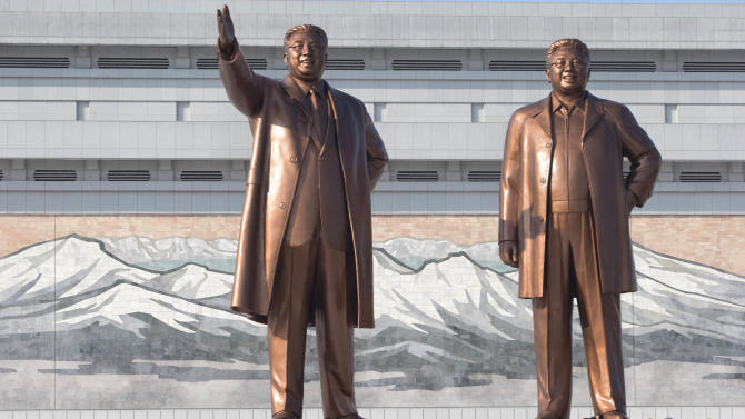 North Koreans bow before the statues of late leaders, Kim Il Sung, left, and Kim Jong Il, at Mansu Hill in Pyongyang, North Korea, Monday, Dec. 17, 2012. Sirens wailed for three minutes at noon Monday in honor of the first anniversary of the death of Kim Jong Il. (AP Photo/Ng Han Guan)