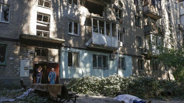 Local residents stand at a damaged apartment block near the body of a victim killed by what locals say was recent shelling by Ukrainian forces in Donetsk