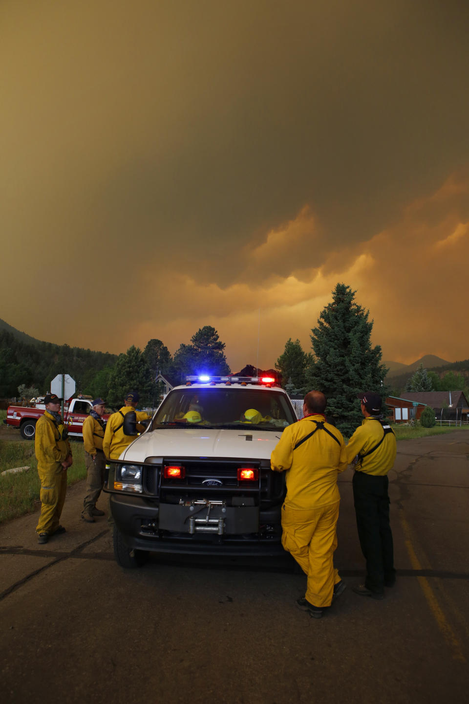Firefighters stage in a residential area to protect homes in South Fork, Colo., as they monitor a wildfire that burns west of town on Friday evening June 21, 2013. The town was evacuated and highway U.S. 160 that passes through it was closed. (AP Photo/Ed Andrieski)