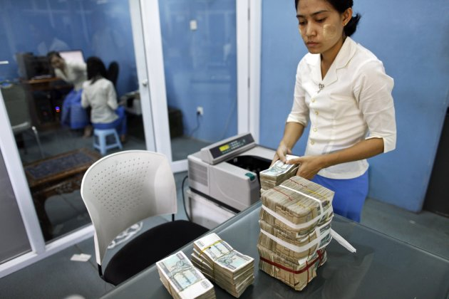 A woman counts Myanmar Kyats at a money changer in Yangon