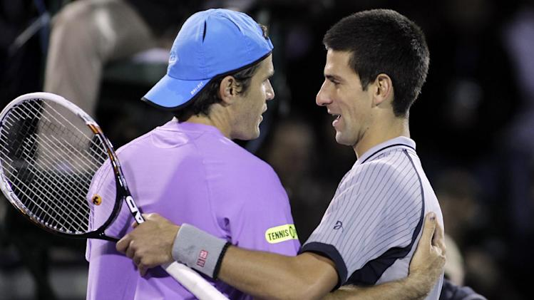 Tommy Haas, left, of Germany, hugs Novak Djokovic, of Serbia, after Haas' 6-2, 6-4 win at the Sony Ericsson Open tennis tournament in Key Biscayne, Fla., Tuesday, March 26, 2013. (AP Photo/Luis M. Alvarez)