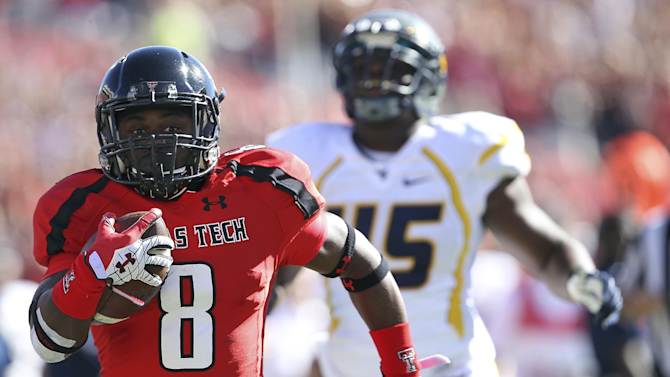 Texas Tech's SaDale Foster breaks free for a touchdown ahead of West Virginia's Eric Kinsey during the first half of an NCAA college football game in Lubbock, Texas, Saturday, Oct. 13, 2012. (AP Photo/Lubbock Avalanche-Journal, Stephen Spillman) LOCAL TV OUT