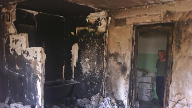 In this image taken Saturday Aug. 16, 2014 a man shows his neighbour's apartment that was burned down after a missile hit a residential area in Lysychansk, Ukraine, during the fighting between the Ukrainian army and the pro-Russian rebels. Lysychansk was retaken by Ukrainian army late last month but has seen sporadic clashes until earlier last week. After months of rebel occupation and weeks of Ukrainian liberation, the residents of Lysychansk this shell-shocked border town say they hope simply to rebuild their former lives _ but fear the return of war to their doorstep. (AP Photo/Vitnija Saldava)