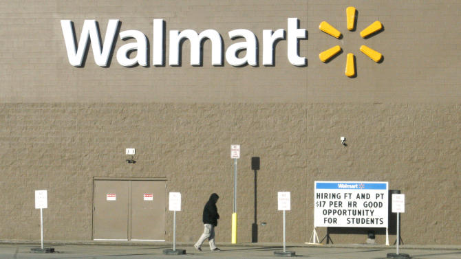A shopper walks next to a Walmart store on Friday, Feb. 28, 2014 in Williston, N.D. near a sign advertising a $17 hourly wage for new employees - a rate higher than in many cities. The Bakken shale fields oil boom has brought about a high cost of living in the area, especially for housing. (AP Photo/Martha Irvine)