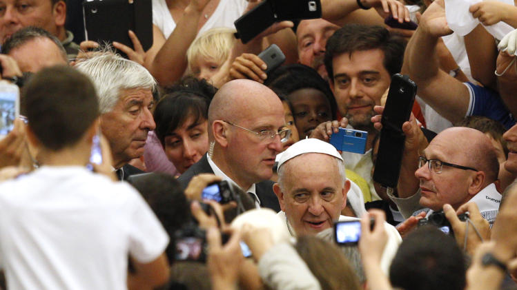 Pope Francis greets faithful as he arrives for his weekly general audience in the Paul VI hall, at the Vatican, Wednesday, Aug. 20, 2014. (AP Photo/Riccardo De Luca)