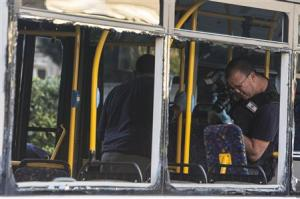 An Israeli police officer takes pictures inside a damaged bus at the scene of an explosion in Bat Yam