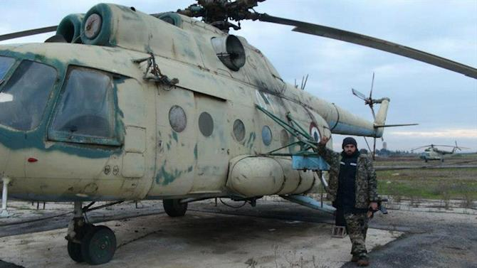 This citizen journalism image provided by Edlib News Network, ENN, which has been authenticated based on its contents and other AP reporting, shows a Syrian rebel posing next to a damaged Syrian air force helicopter, at Taftanaz air base that was captured by rebels, in Idlib province, northern Syria, Friday Jan. 11, 2013. Islamic militants seeking to topple President Bashar Assad took full control of a strategic northwestern air base Friday in a significant blow to government forces, seizing helicopters, tanks and multiple rocket launchers, activists said. (AP Photo/Edlib News Network ENN)
