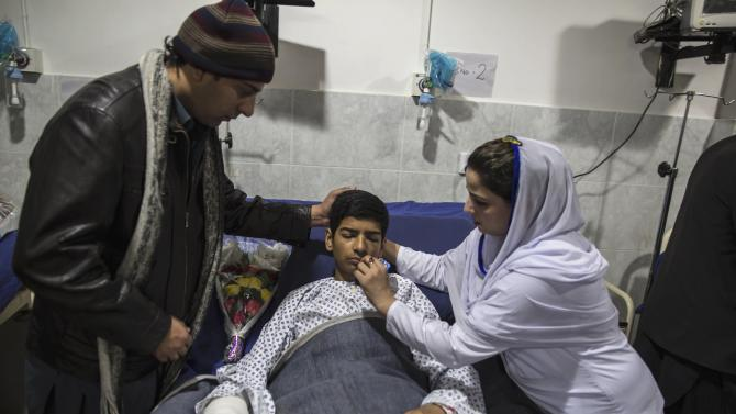 Mehran Khan, 14, who survived an attack by Taliban gunmen on the Army Public School, received his medicine as he lies on a hospital bed in Peshawar