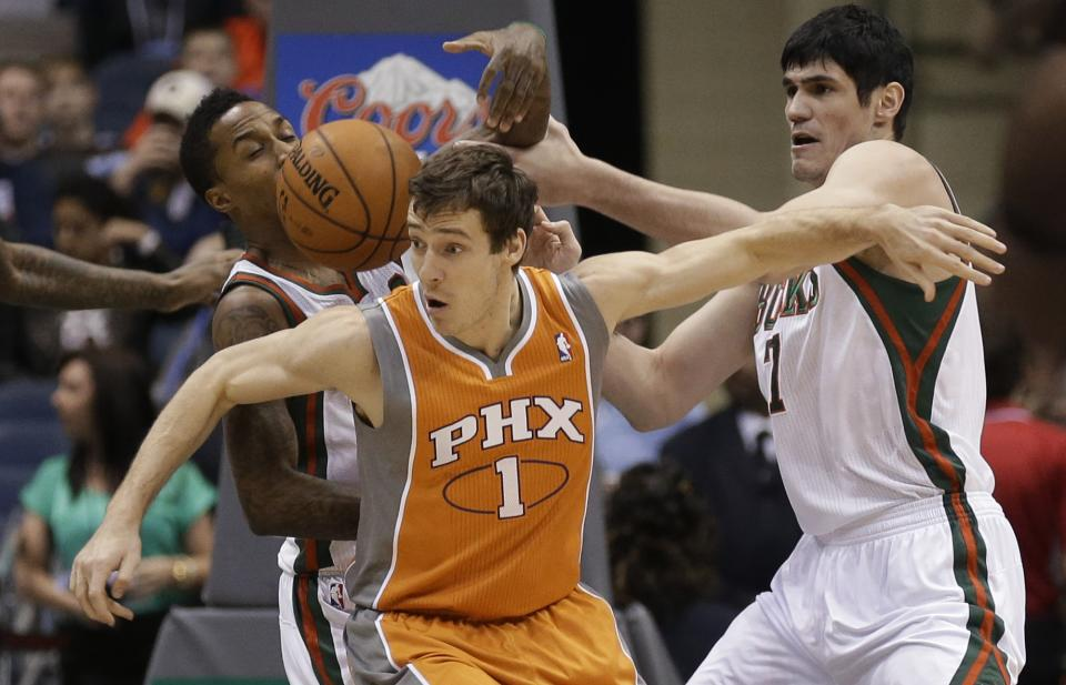 Milwaukee Bucks' Brandon Jennings, left, Phoenix Suns' Goran Dragic (1) and Bucks' Ersan Ilyasova, right, reach for a loose ball during the first half of an NBA basketball game Tuesday, Jan. 8, 2013, in Milwaukee. (AP Photo/Jeffrey Phelps)